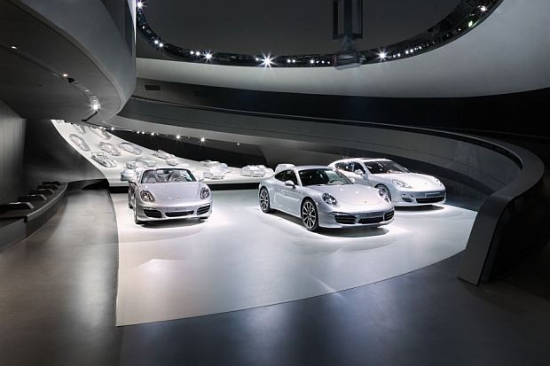 An elliptical ramp leads to the exhibition area displaying the Porsche cars