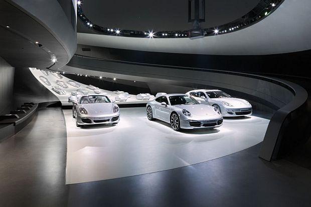 Una rampa elíptica baja hasta la zona de exposición donde se encuentran los vehículos Porsche.