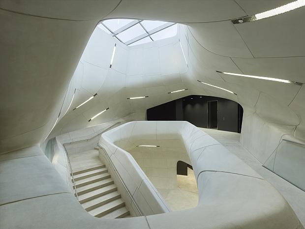 Superficies suaves y envolventes te encaminan hacia el interior del edificio