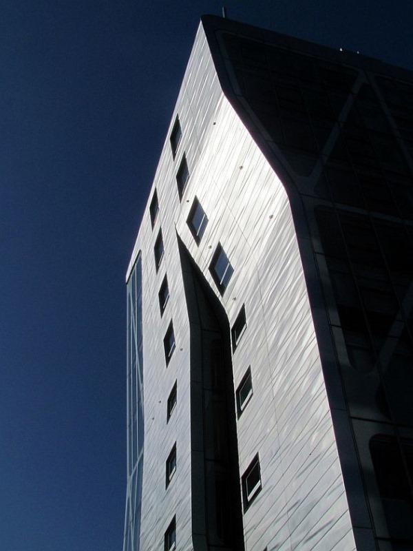 La fachada de vidrio y acero se abre como una grieta en el lado sur